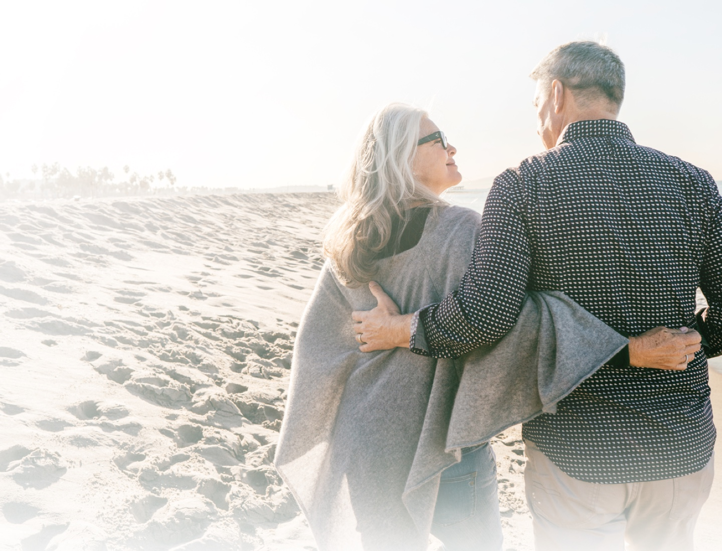 Older man and woman walking on beach