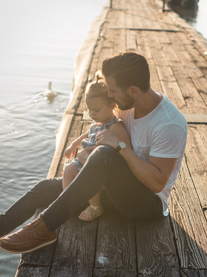 Father and daughter sitting on a pier