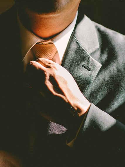 Man in suit adjusting tie