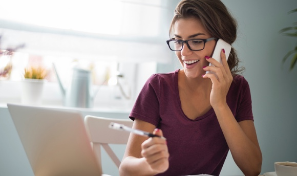 Image of a smiling young woman on the phone with a client